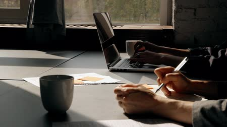 iş istasyonu : Hands of two smart, confident and successful woman on desk table indoor office with modern interior. Concentrated female in formal wear making notes online using laptop and on paper Stok Video