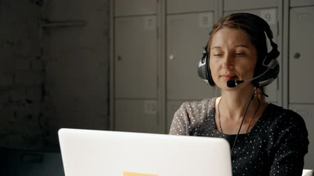 amadurecer : Intelligent and successful female looking on laptop display and speaking with client. Call center operator using headset and sitting behind work desk indoor workstation with simple interior Stock Footage