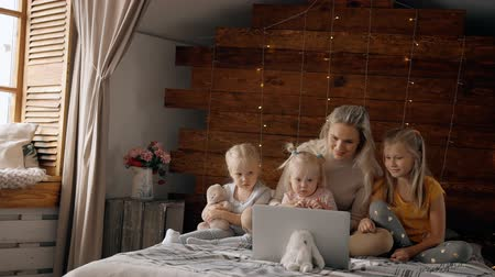 отпрыск : Lets spending weekend together. Attractive, glad and smiling mother using laptop with her little kids. They sitting on comfort bed inside modern interior flat with soft and natural daylight room