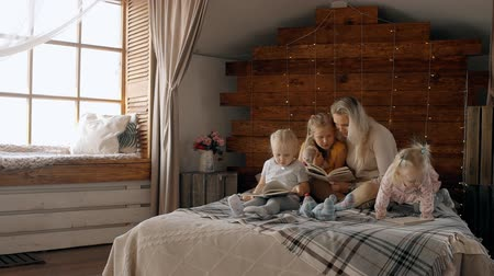 descuidado : Concept of happy family. Beautiful and attractive mother with her three little kids reading book. They sitting on comfort bed indoor bright and light modern interior room in loft style