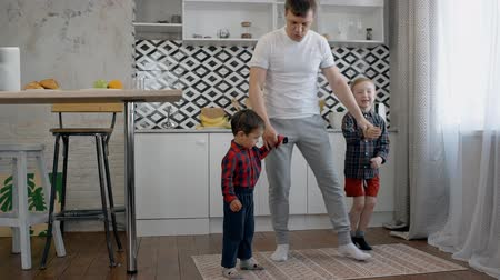 leaping : Lets dance together. Smiling adult father dancing in kitchen room inside cozy house with his two little sons. They spending weekend at house with fun