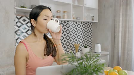 confortável : Young casual looking woman is sitting, drinking coffee and working online. Networking connection and messaging wireless technology for charming working designer. Modern digital computer for business at home.