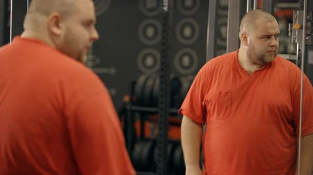 лучше : Disappointed, dissatisfied, sad and unhappy man wearing in orange tee-shirt standing inside modern city sport gym. He looking at himself at mirror before start training for better shape