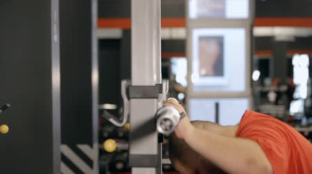 o : Focused, concentrated, good-looking young and strong man wearing in colorful orange tee-shirt standing inside new sport gym. He ready doing squat exercise with heavy metal barbell