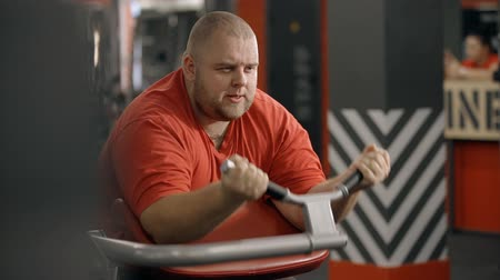 honte : Attractive and good-looking man wearing in orange tee-shirt sitting inside new sport gym on comfort training apparatus. He using heavy barbell to making hard exercise and achieve better body shape