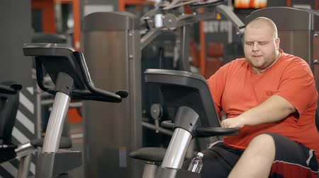 o : Attractive, calm, handsome young man wearing in colorful orange t-shirt sitting on exercise bike inside modern and large sport gym. He starting workout from easy warm up training Stok Video