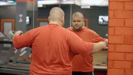 o : Nice-looking, positive, attarctive and overweight man wearing in orange shirt standing inside modern and large sport gym. He looking on mirror at himself and checking his body shape