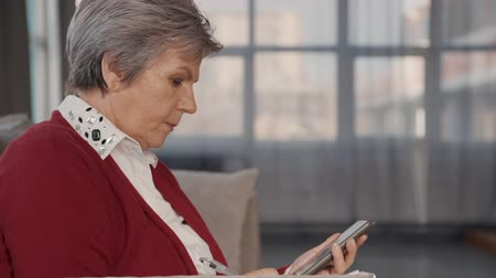 napirend : Profile side view of confident and beautiful pensioner woman in casual clothes sitting on couch in apartment room. She looking at her smart telephone and typing text message on display Stock mozgókép