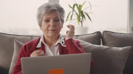 kompakt : Confident, focused and concentrated retired woman in casual wear sitting on couch in apartment room. She wearing earphones in her ears and looking at modern laptop monitor with calm face