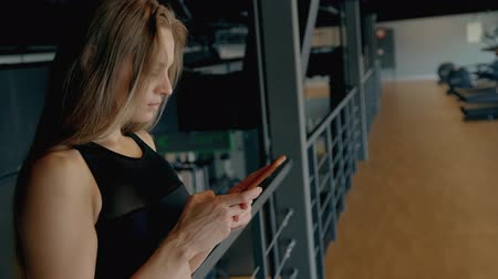 ona : Profile side view of young woman with blond hair wearing in comfort outfit clothes training inside sport center with modern interior. She making pause to texting message on her cellular
