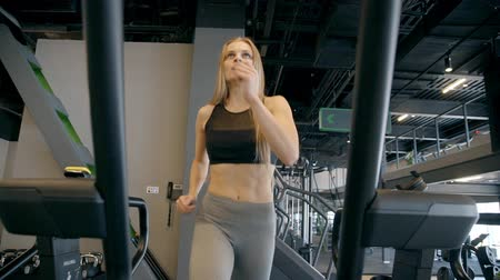 tornacipő : Young sexy woman is running very intensive training on treadmill. Exercise machine equipment for successful and useful workout at gym. Healthcare active lifestyle for energy people. Cute caucasian girl.
