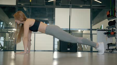 bodyweight : Profile side view of good-looking young woman wearing in comfort outfit clothes and trendy shoes, training inside sport center with modern interior. She wring out and standing in plank position