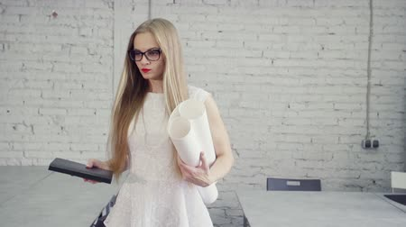 архитектор : Confident and success businesswoman in formalwear clothes white dress holding agenda and blueprint in her hands. She walking in modern loft interior with bright and natural soft light Стоковые видеозаписи