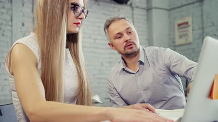 нетбук : Two colleagues discuss new project and looking at laptop. Man and businesswoman in formalwear clothes sitting on simple and comfort chair behind office desk in bright modern interior
