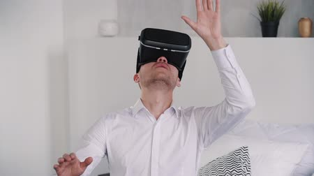 telemedicine : Exited and brunet hair man in white formal wear shirt sitting on bed in bright apartment with light interior. He playing in games and looking up in 3d modern virtual reality helmet