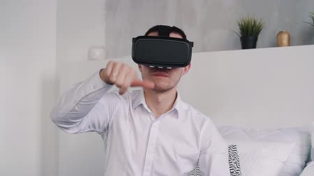 o : Focused, concentrated and serious man in white shirt sitting inside room in apartment or modern flat. He wearing in new, modern helmet of virtual reality and making gesture by hand