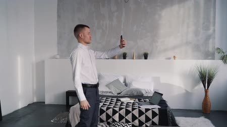telemedicine : Real estate man in white shirt and black pants walking inside bedroom with nature soft light. He holding his modern smartphone in hand and showing new flat to his costumers and clients Stock Footage