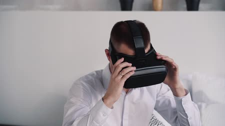 flat head : Man with calm face sitting in bright room and nice light flat in white shirt or formal wear clothes. He wearing modern and new virtual reality helmet on his head and ready to playing in games Stock Footage