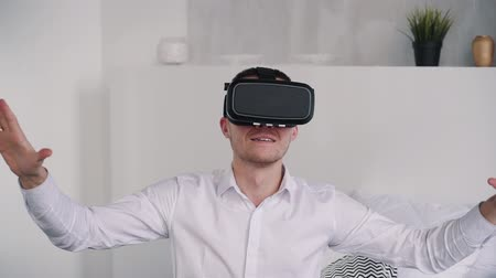 Wow, its so real. Glad and cheerful man in formal wear clothes sitting in bedroom with nature soft light. He resting at home after long work day and playing at games in virtual reality helmet 動画素材