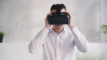 telemedicine : Confident, serious, focused and brunet hair man in formal wear clothes standing against white wall in room with nature soft light. He wearing modern virtual reality helmet on his head Stock Footage