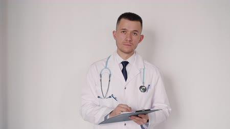 telemedicine : Concentrated, focused and serious smart doctor fills paper form document after visiting new patient. He looking on blank and standing against white wall in bright light interior room Stock Footage