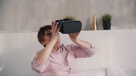 telemedicine : Exited and wondered middle aged woman in pink shirt sitting on bed in bright apartment with light interior. She looking impressed and remove modern virtual reality helmet from her head