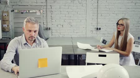 discurso : Handsome man using laptop and sit near young focused lady in formal wear. They solves routine tasks, sitting behind workplace on chair in bright light modern interior with natural soft daylight