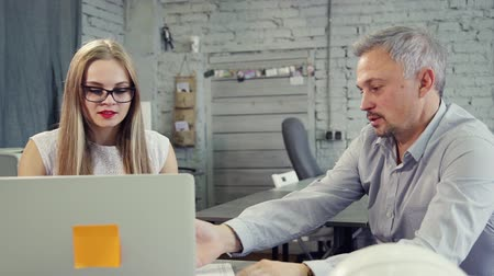 colegas : Cooperation for brainstorming. Happy assistant lady in nice white formal wear looking at speaking matured man inside office. She sitting behind workplace on chair in modern loft interior Stock Footage