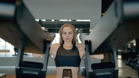 press wall : Sweet, gorgeous, nice and adorable lady with long blond hair wearing in stylish sportswear. She workout inside gym of modern sport center, working with shoulders on special machine
