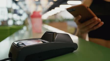 payment terminal : Young woman is buying something and making payment with smartphone. Terminal money device is wireless and useful gadget for modern business. Glamour financial shopping.Female customer using mobile phone.