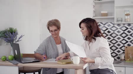 образованный : Nice-looking and friendly mature and mid-aged woman writing and checking paper blanks at kitchen. They spending free time together in in bright and stylish modern interior with soft daylight