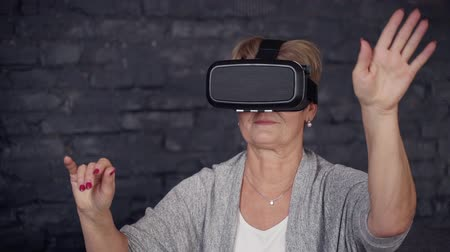 amadurecer : Senior woman with calm face sitting on couch or comfort sofa inside modern and comfort room in loft style. Female relaxing and spending free time at home in virtual reality glasses Stock Footage