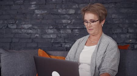 watching news : Nice-looking and friendly mid-aged woman spending day with laptop. She looking at monitor with calm face and sitting on couch in modern apartment with trendy interior and black brick wall