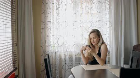 conferencing : Blond woman reading news on her smartphone at home. Youn lady sitting at the table in bright dining room with two windows and scroling the screen of her mobile phone by the finger. Portrait. Stock Footage