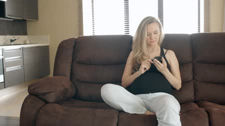 conferencing : Young pregnant woman is using smartphone sitting on sofa in home interior, future mother in casual clothes is holding gadget, browsing web, having time on soft couch in apartment. Concept: pregnancy, technology, lifestyle.