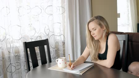 atualizar : Beautiful lady writing a list for shopping at home and her son standing near. Young mother with blong hair sitting at the wooden table in bright living roon and taking notes in notebook.