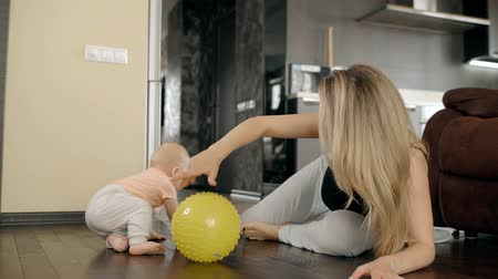 Blond mother twisting yellow ball playing with her son at home. Young beautiul woman lying on the wooden floor in living room and her baby trying to catch the toy by his tiny hands. Family enjoing th