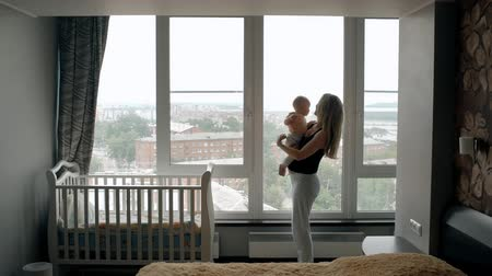 primeiro plano : Young mother holding her baby, standing in front of the window at home. Woman and her little kid looking through the glass to the city, being in modern child room near the bed.