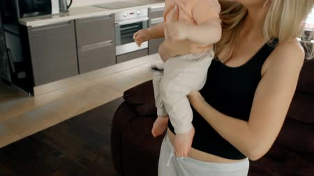 babysitter : Mother and her baby son spanding time at home together. Young blond woman holding her child and hugging him, standing in the kitchen with modern interior. Little kid in pink t-shirt looking around.