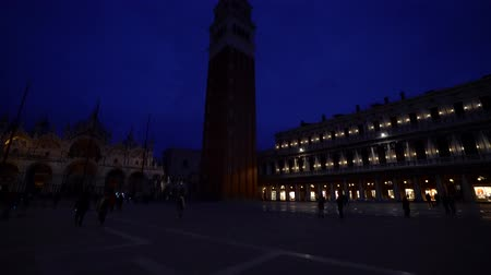 Piazza San Marco or St Marks Square principal public square of Venice, Italy at night. Tourists people crowd walking San Marco square at night, evening, dusk, blue hour 4K
