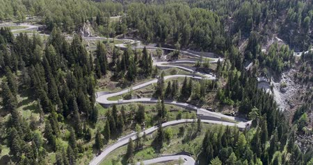 undulating : Aerial view of mountain serpentine road with trucks and cars driving on zig zag go up and down in Europe Switzerland 4K Stock Footage