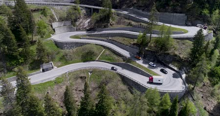yılantaşı : Aerial view of mountain serpentine road with trucks and cars driving on zig zag go up and down in Europe Switzerland 4K Stok Video