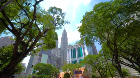 KUALA LUMPUR, MALAYSIA - May 15, 2018: The Petronas Towers or Petronas Twin Towers a popular tourists attraction rise above green tropical trees. 4K Wideo