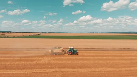 combinar : JUSSEY, FRANCE - Aug 02, 2018: Aerial view flying over wheat field and combine harvester tractor with trailer that makes stacks of wheat at summers day 4K.