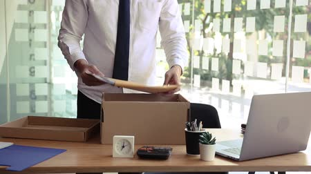 licenziamento : Young male employee standing near work table putting his stuff from in carton box belongings after being dismissed resignation leave company. Filmati Stock