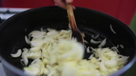 Thin sliced onion cooking in the frying pan