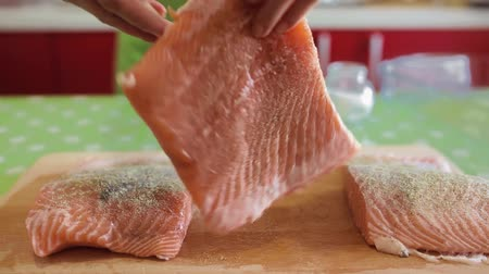 Closeup of woman hands seasoning salmon fillets