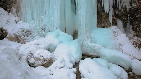 Panning fottage of a waterfall in the winter with icicles