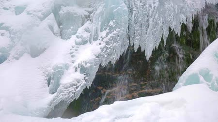 Sliding fottage of a waterfall in the winter with icicles