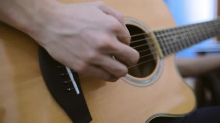 Closeup of the hands of a young man playing guitar